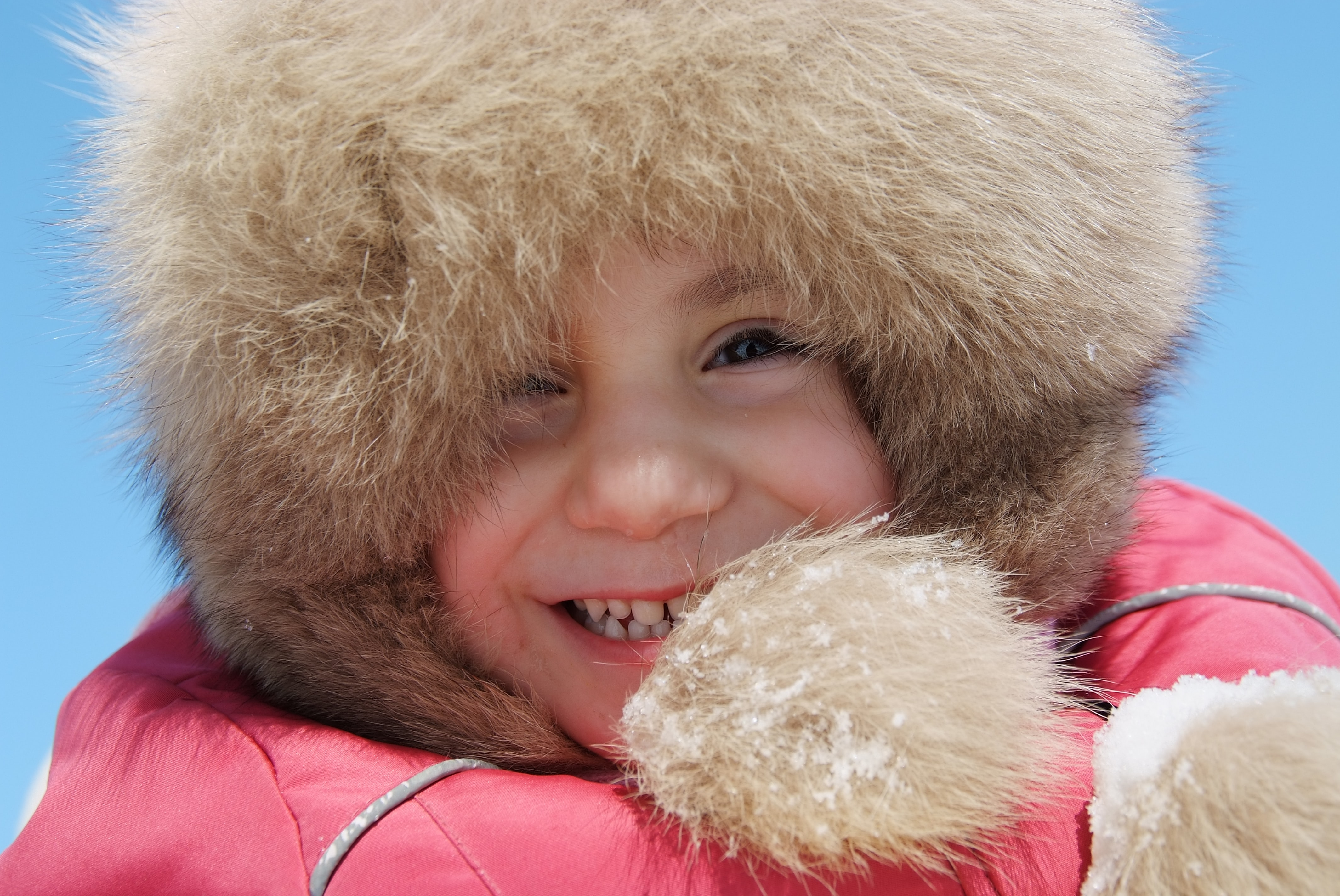 A child wearing a fur-lined hood smiles against a blue sky in Kazan