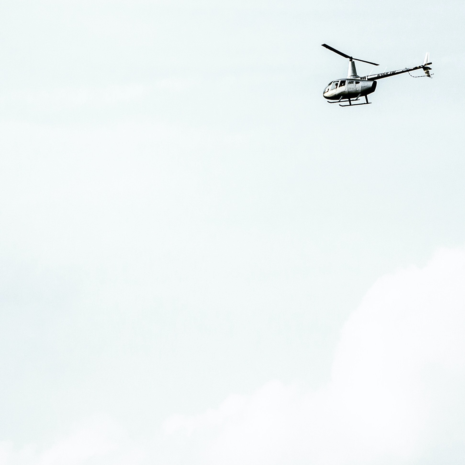 A white helicopter against a pale sky