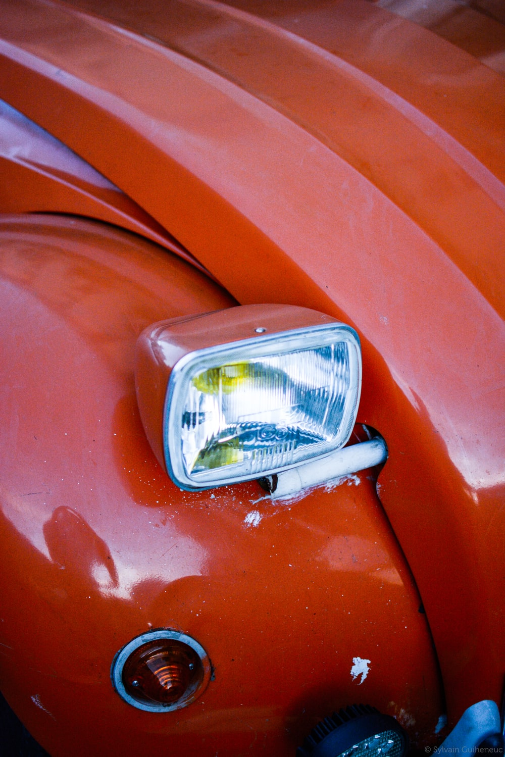 close view of red vehicle with headlight