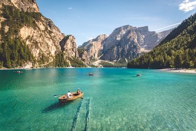 three brown wooden boat on blue lake water taken at daytime