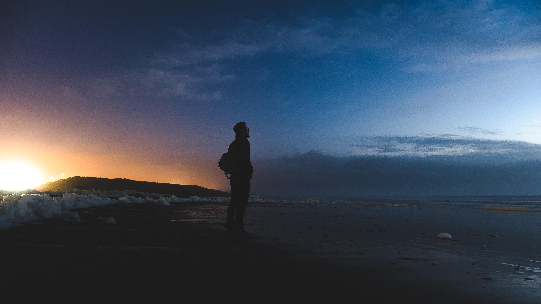 man standing on seashore facing sea