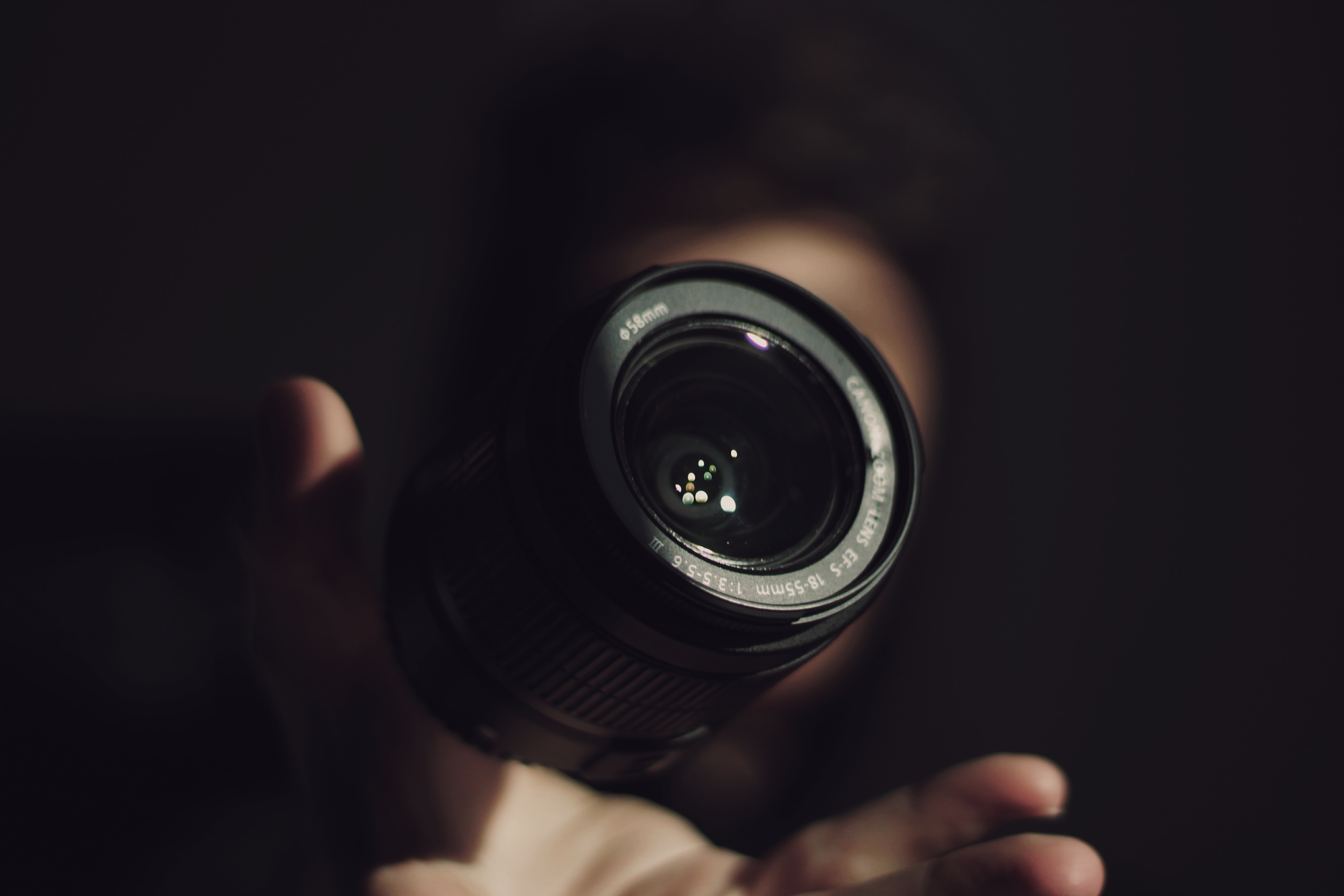 58mm Canon DSLR camera floating over a person's hand