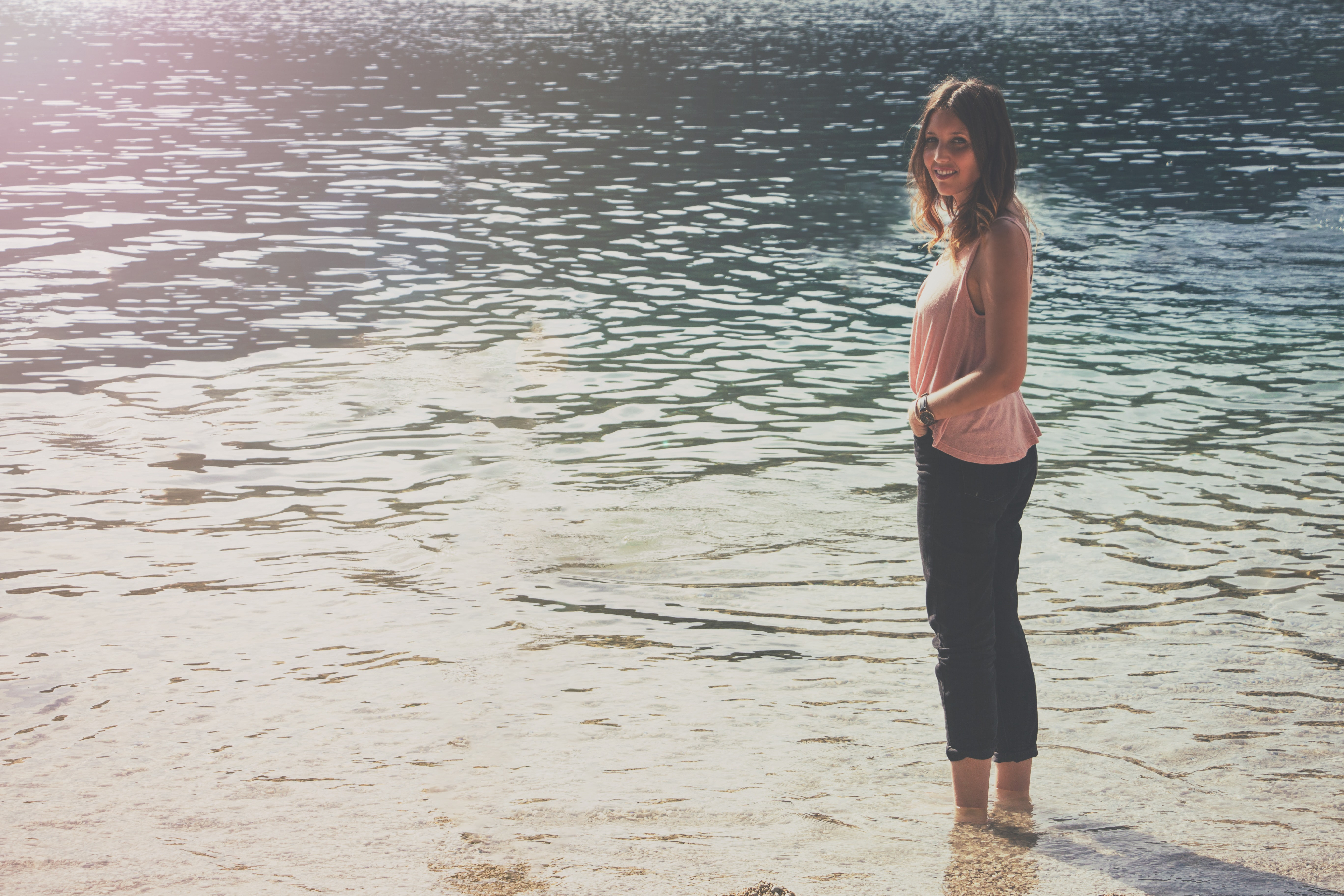 woman in pink sleeveless top and black cargo pants standing on body of water