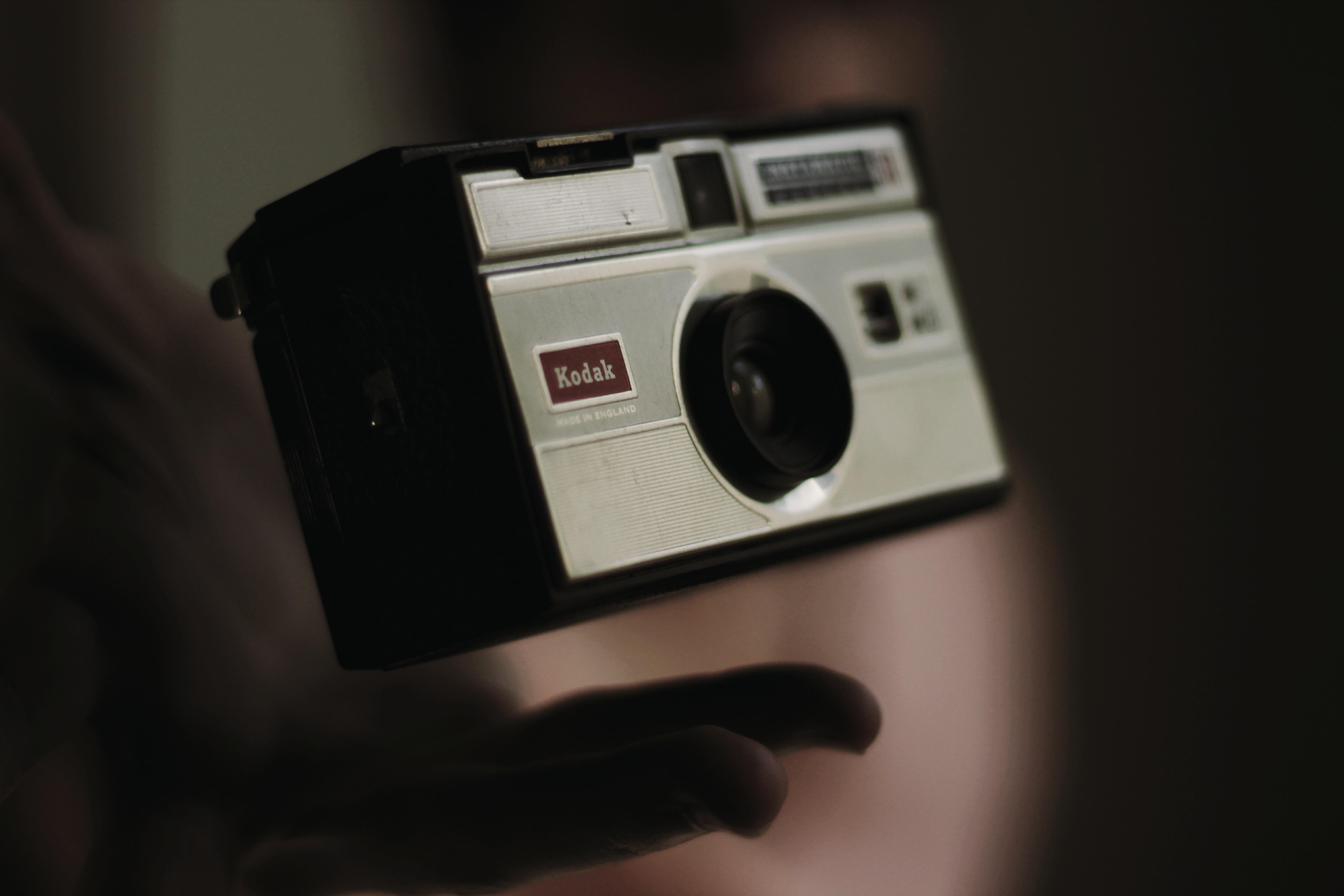 person throwing a gray and black Kodak camera