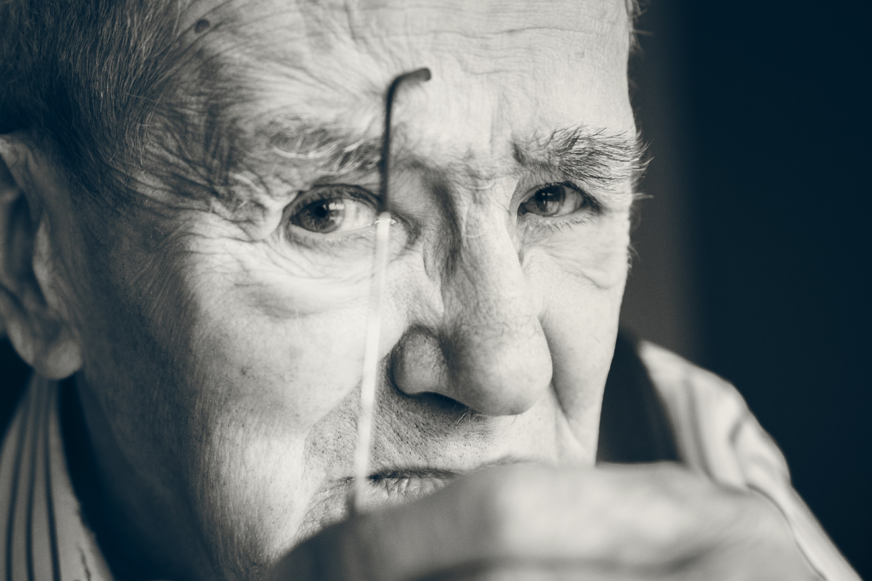 Black and white close up of serious old man with wrinkles removing glasses in Tournai