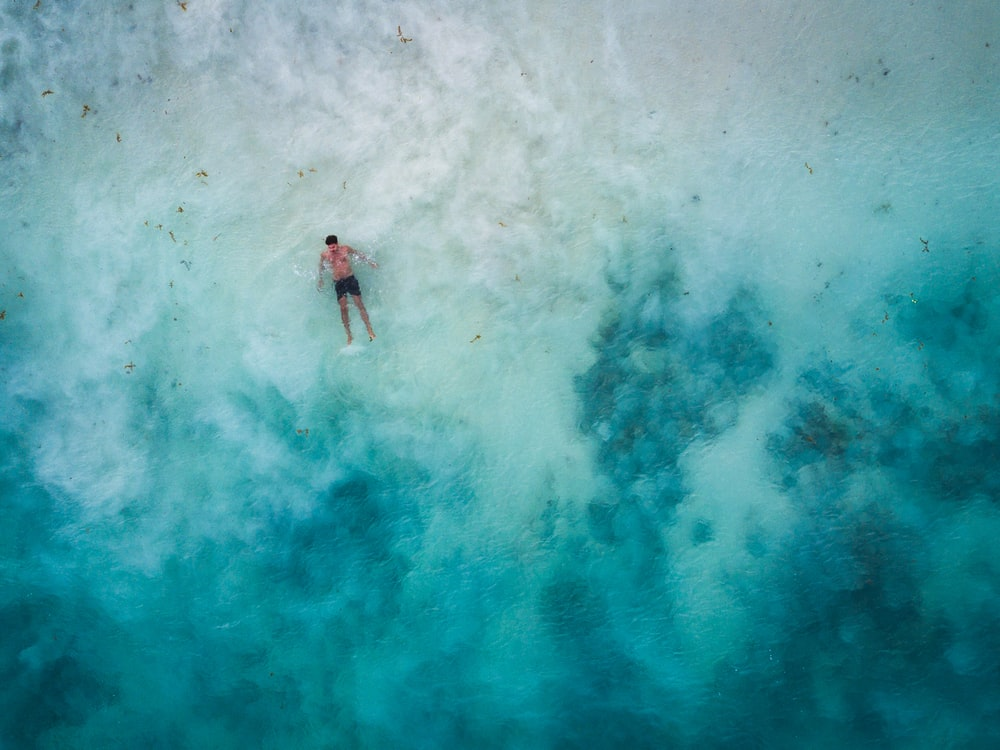 high-angle photography of man in body of water