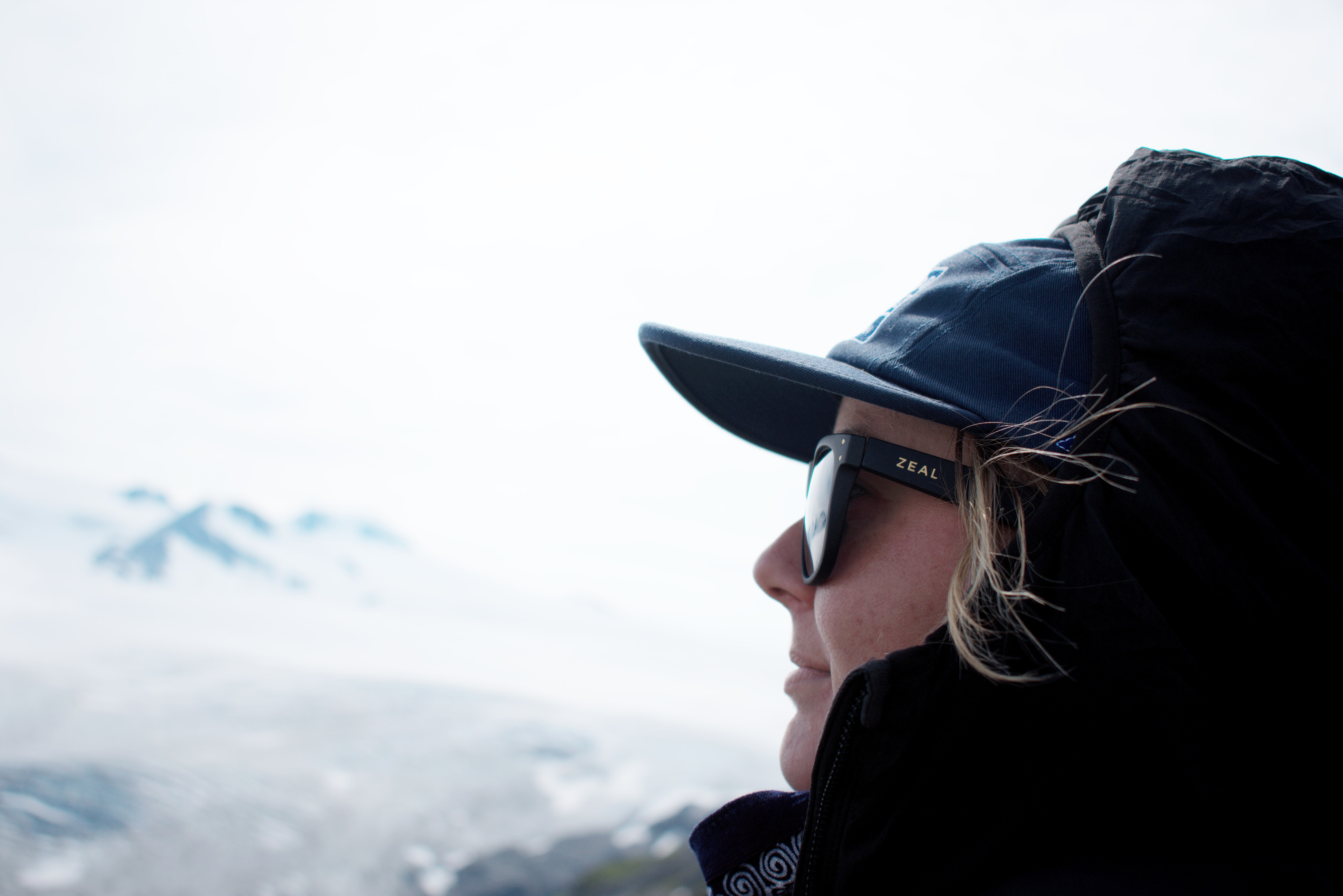 A person in a baseball cap, sunglasses, and hood looks into the distance at Exit Glacier