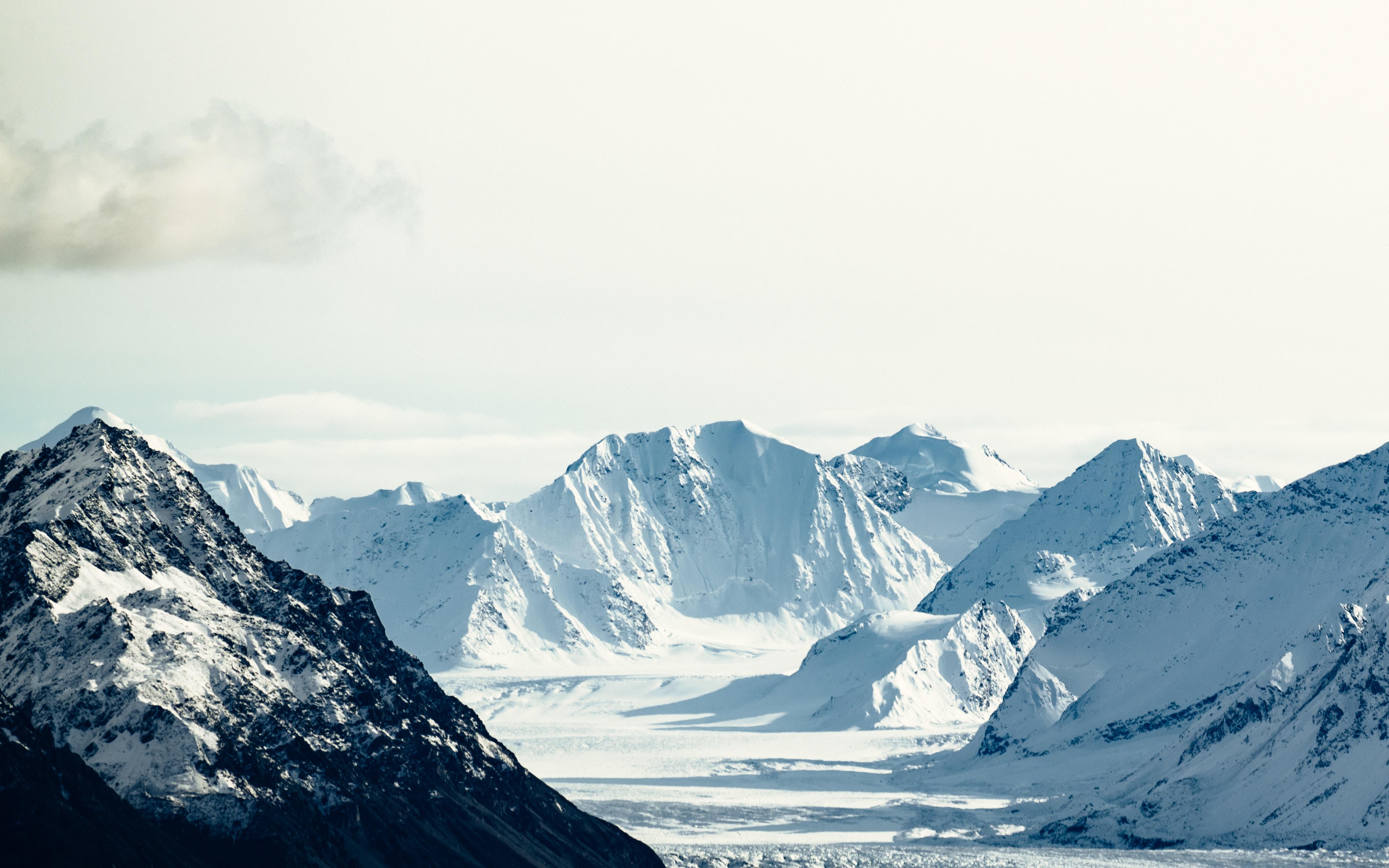 Snowy mountain range under white sky