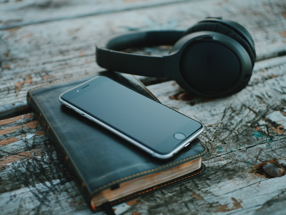 space gray iPhone 6 on book near black wireless headphones
