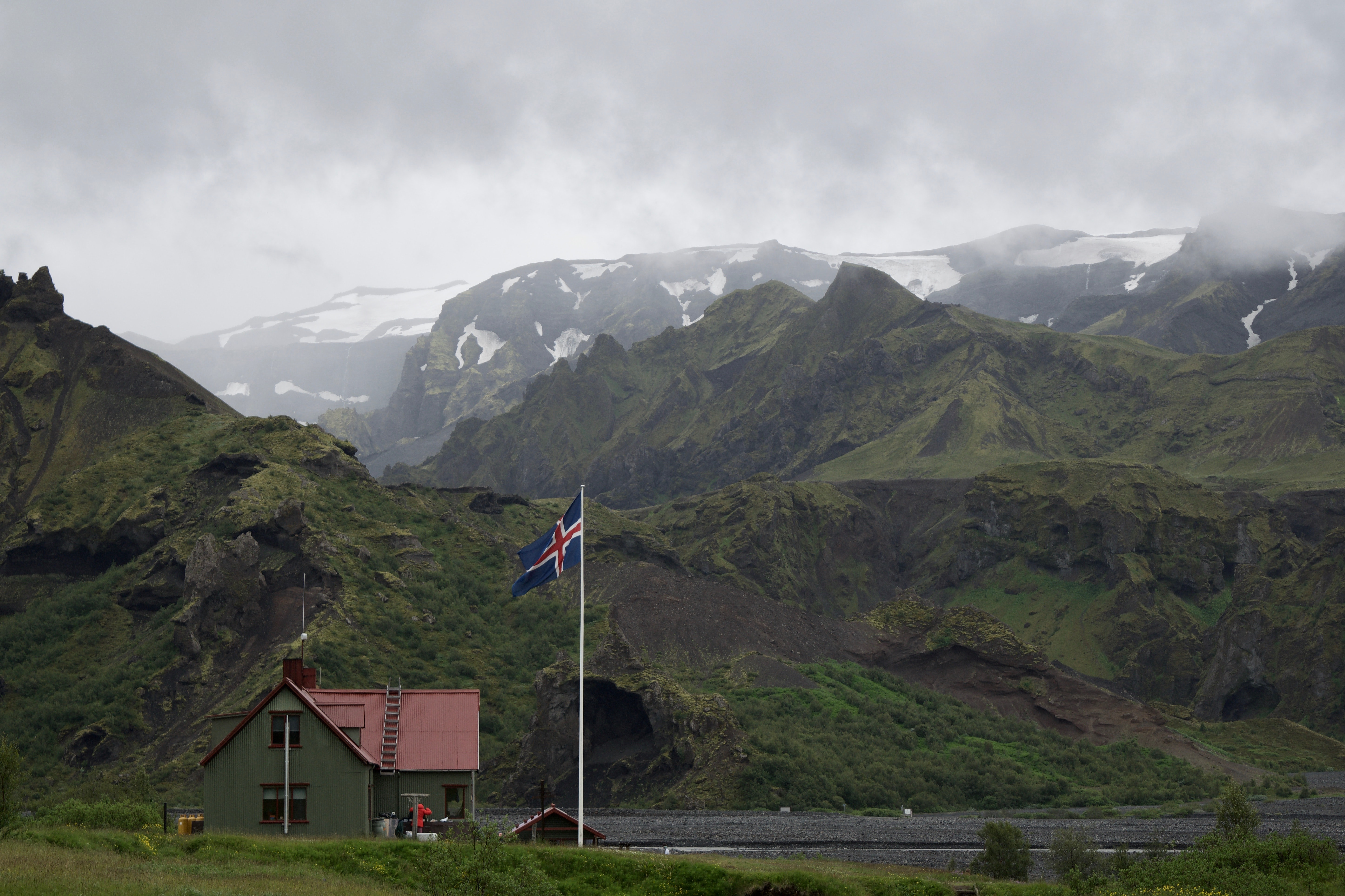 white concrete house with white, blue, and red cross flag near mountain range covered in green vegetation at daytime
