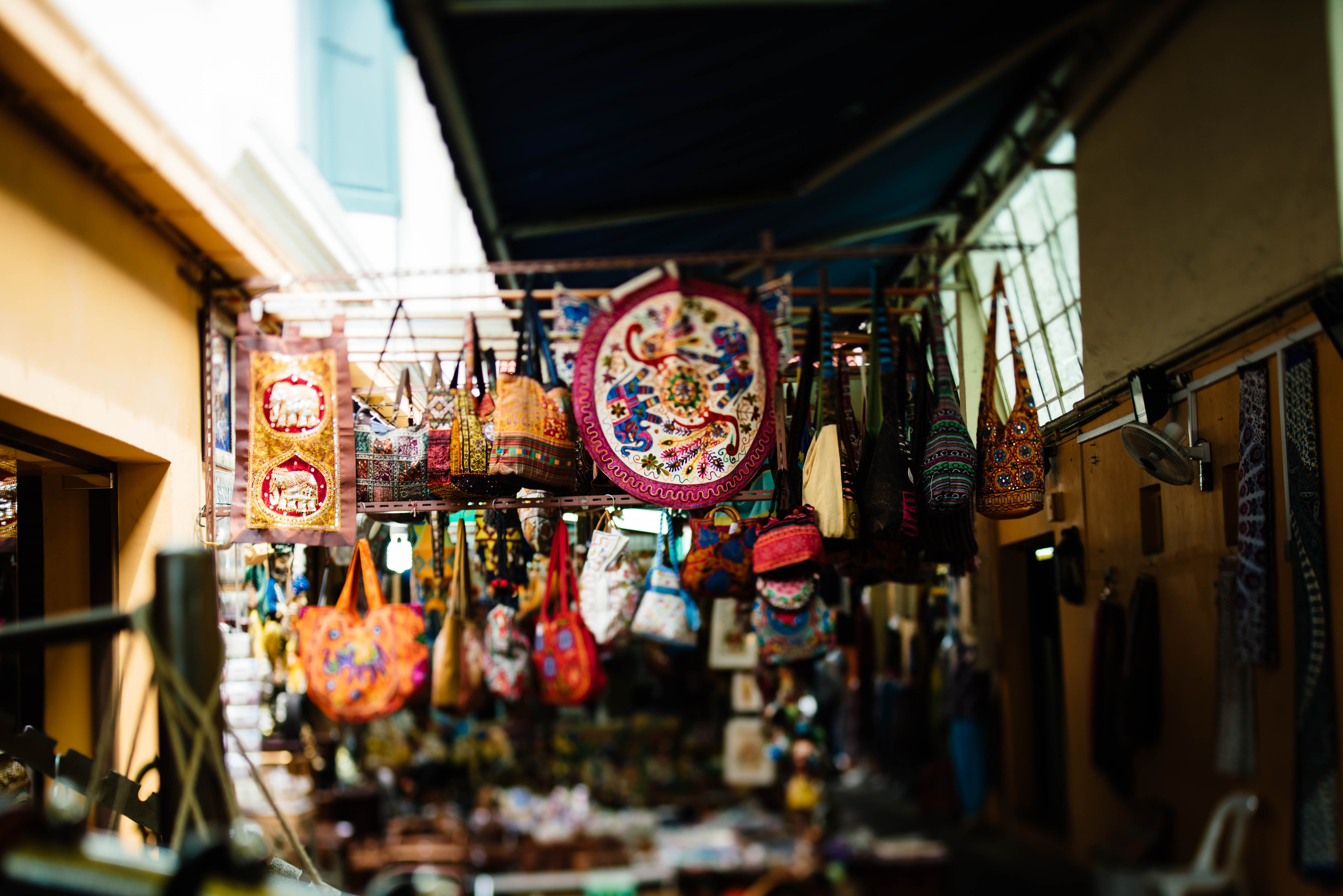 A street market stall selling various pattered and colored satchels and handbags in a narrow alley