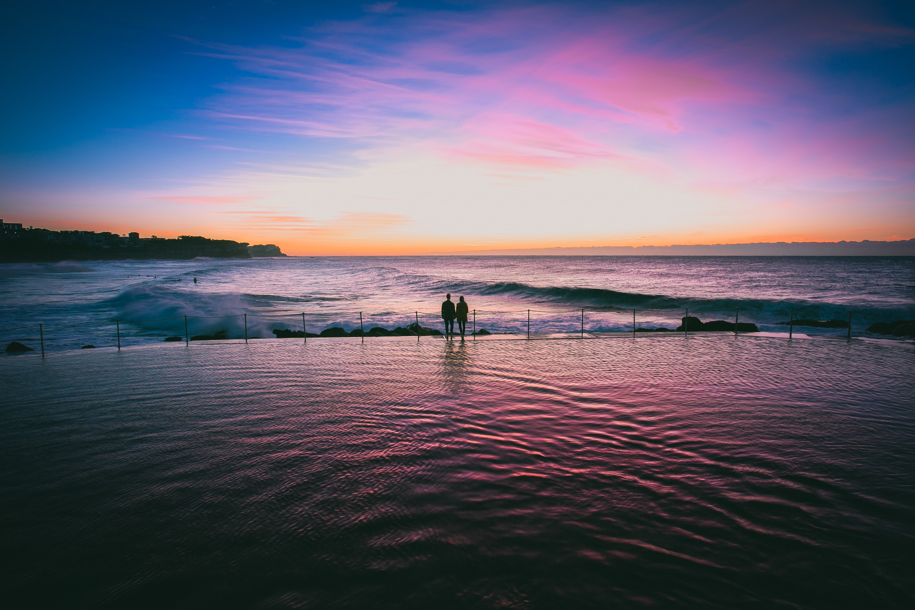 Couple holding hands at sunset on the edge of infinity pool by the ocean at Bronte Beach