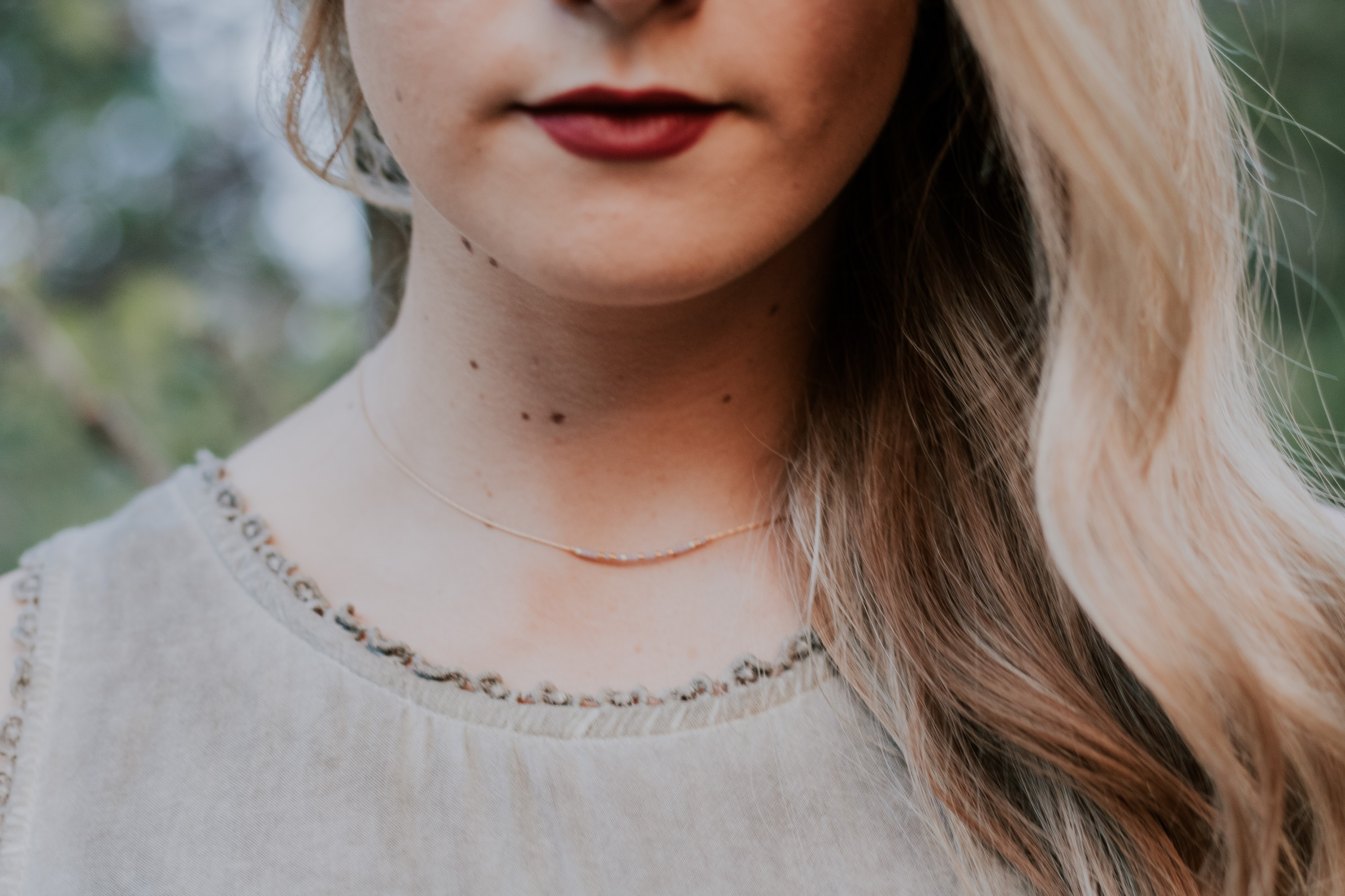 A close-up of a woman's chin. She wears a necklace and dark red lipstick.