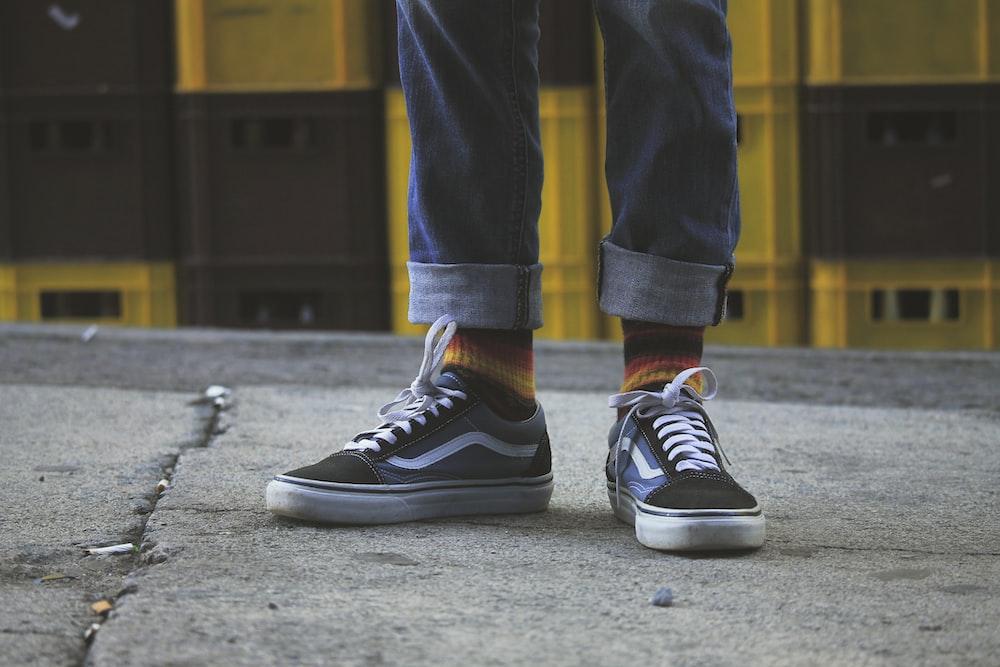 person wearing black Vans Old Skool shoes