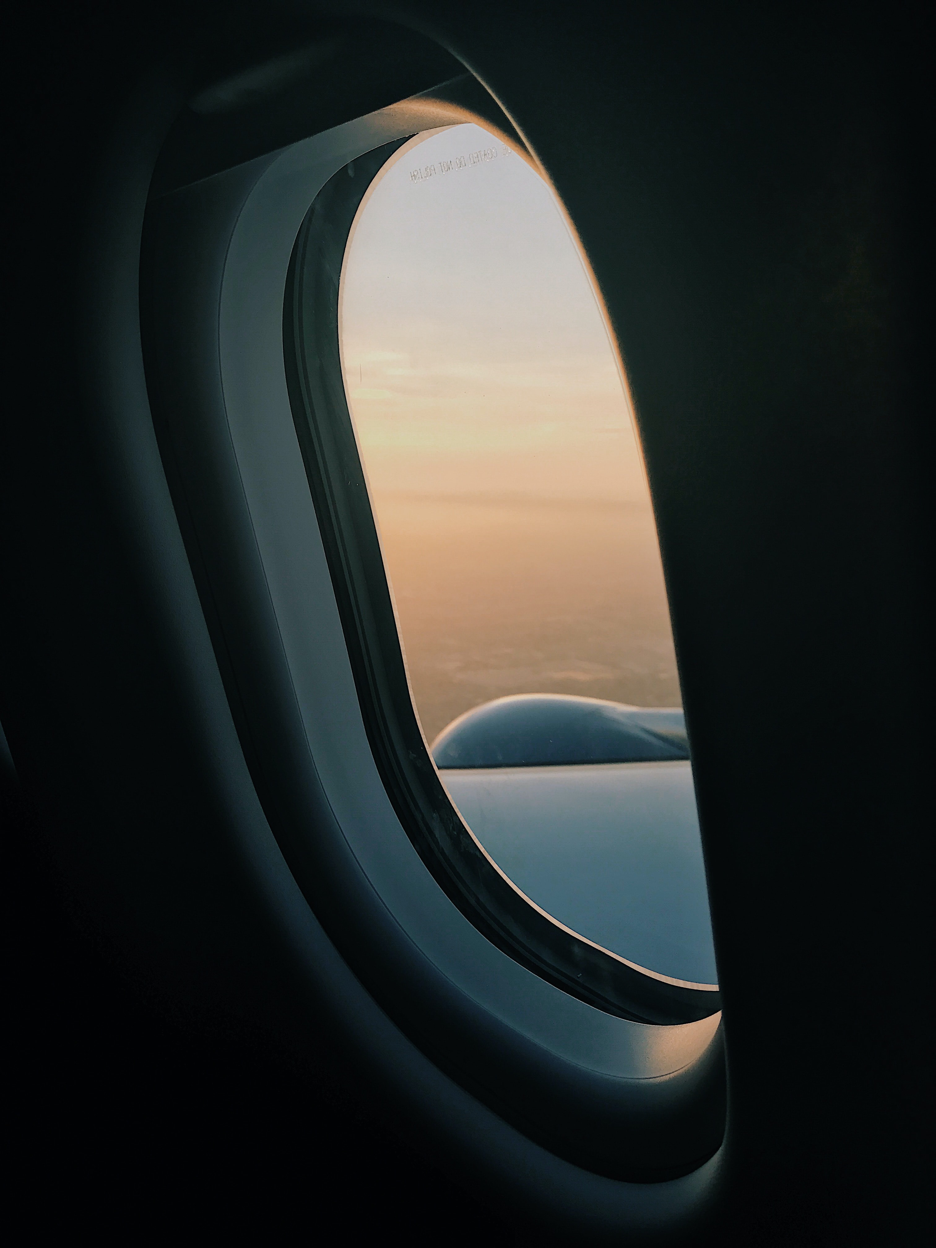 View through an airplane window on the sky at sunset
