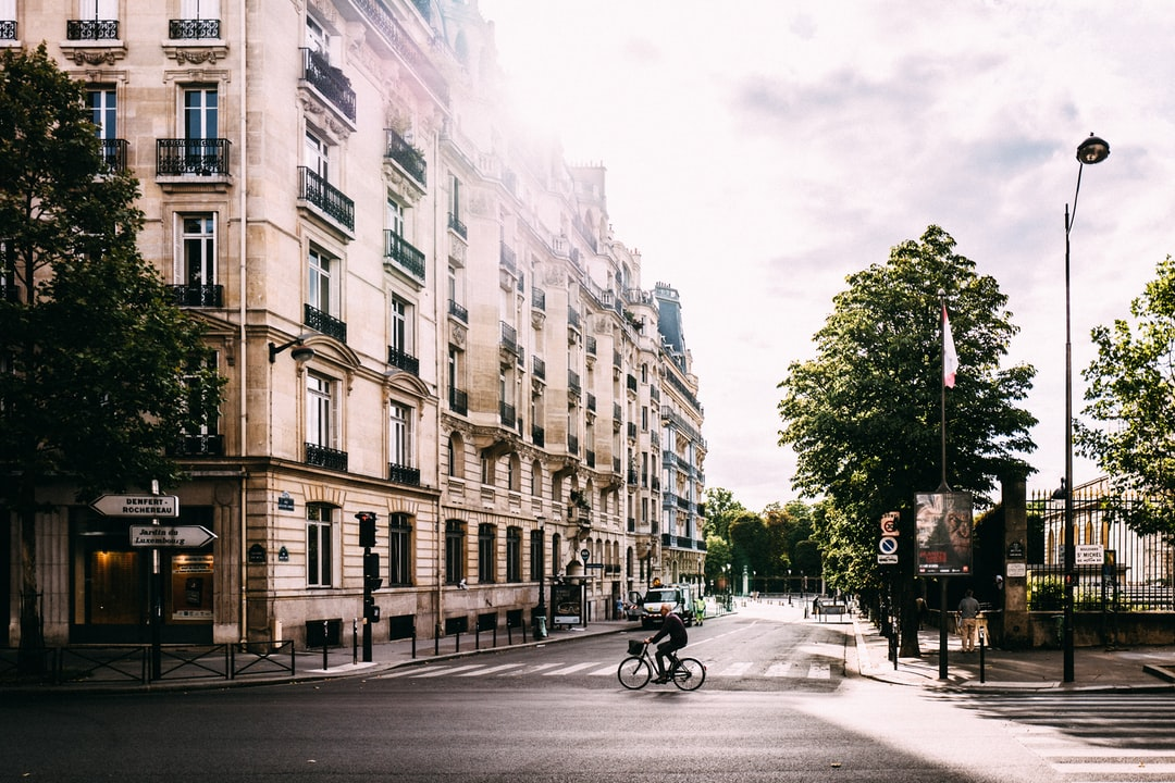 man riding bike on middle of road near white concrete building in Luxembourg Gardens France