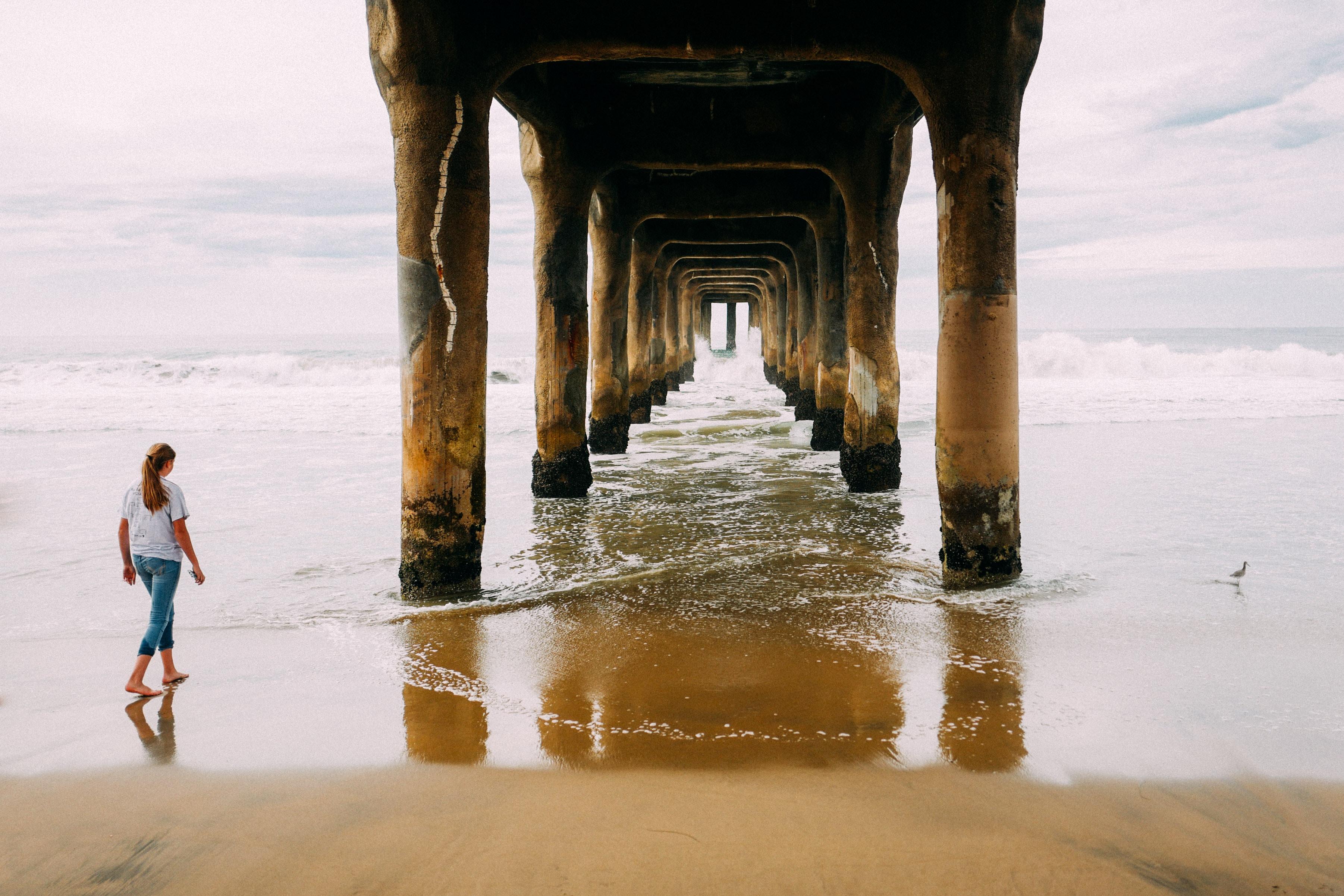 woman walking on seashore towards bridge pillars