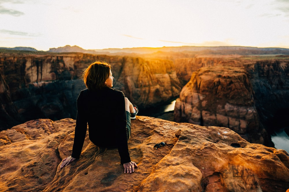 woman sitting on top of cliff