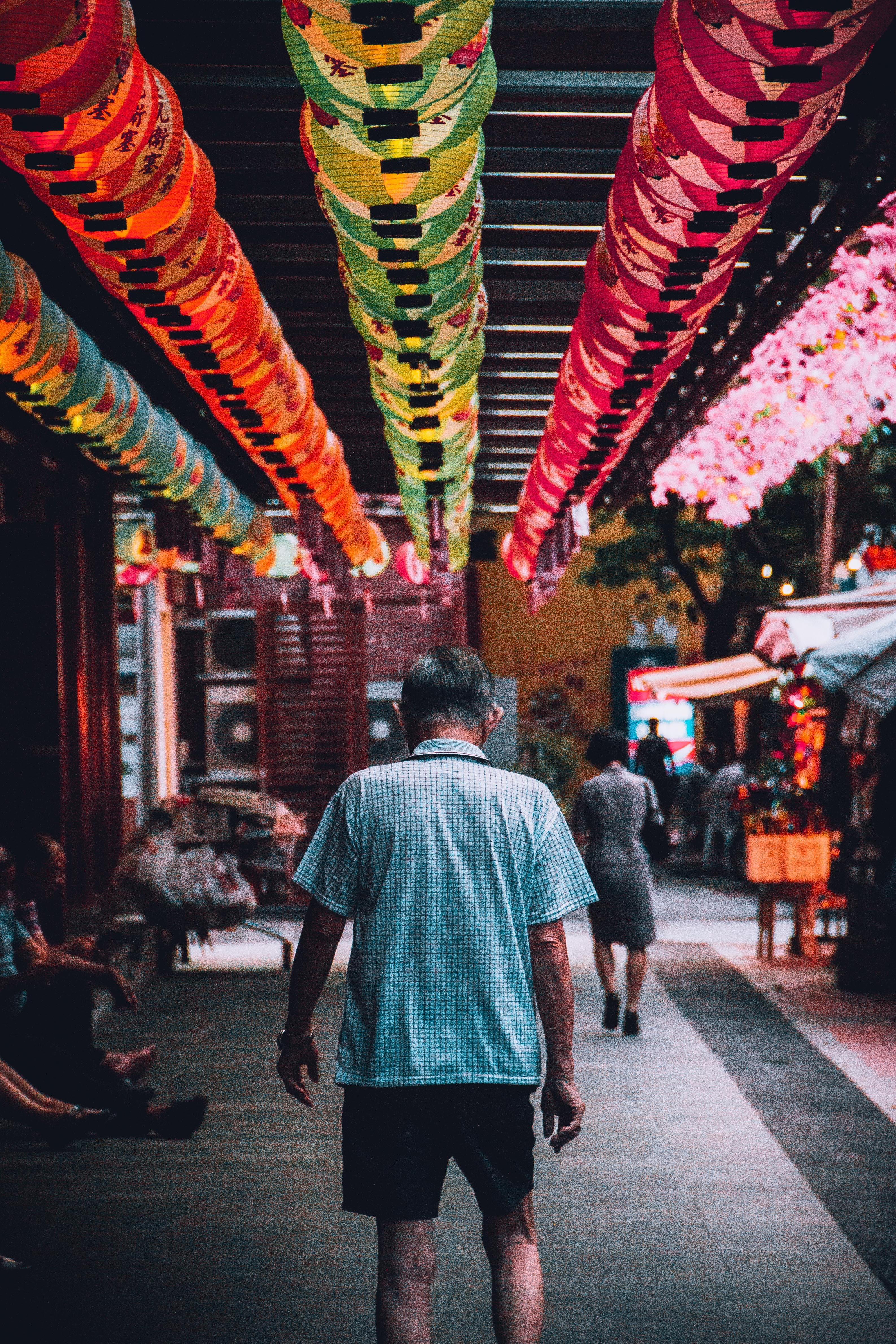 An elderly man strolling in the marketplace in Singapore's Chinatown