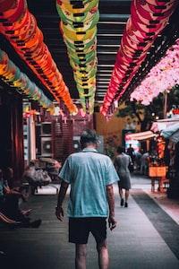 man in collared shirt walks between building during daytime