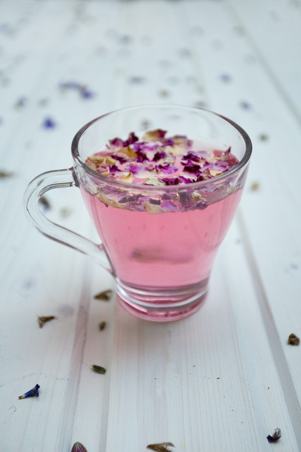 clear glass cup surrounded by petals