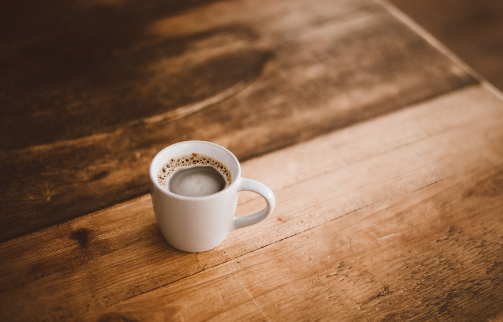 white ceramic mug with coffee on brown wooden table