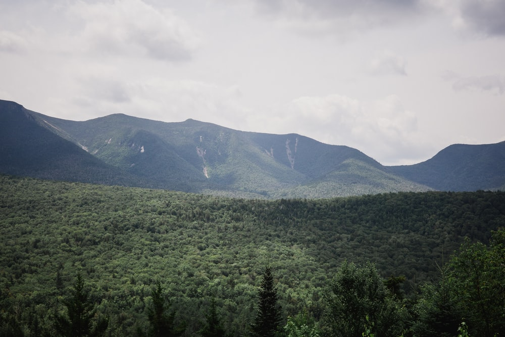 green and black mountains under white and gray sky at daytime