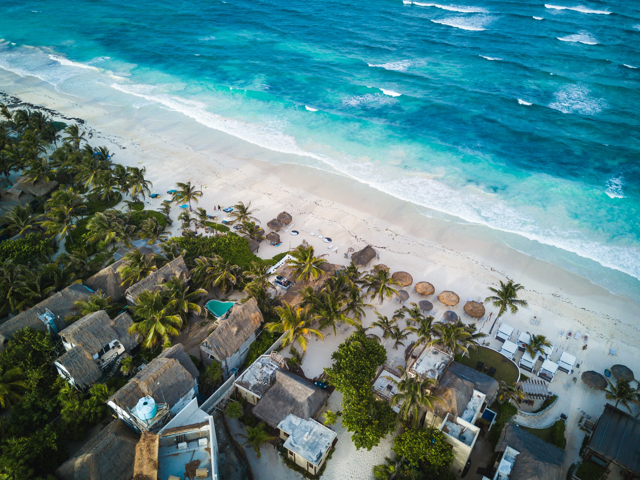 A drone shot of a resort, umbrellas, lounge chairs, and the ocean in Tulum, Mexico