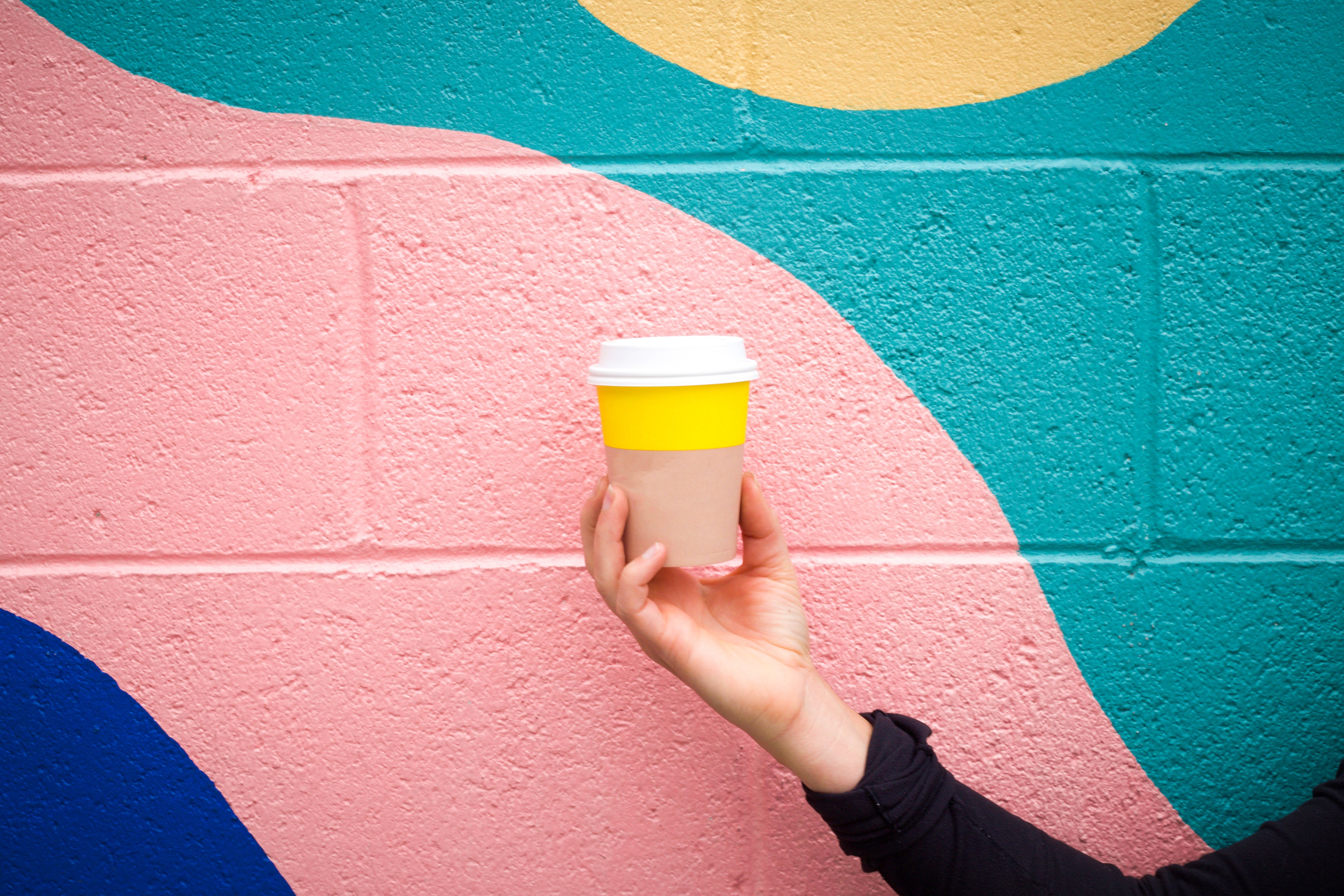 Person holding a plastic coffee cup in front of colorful wall at Venice Beach