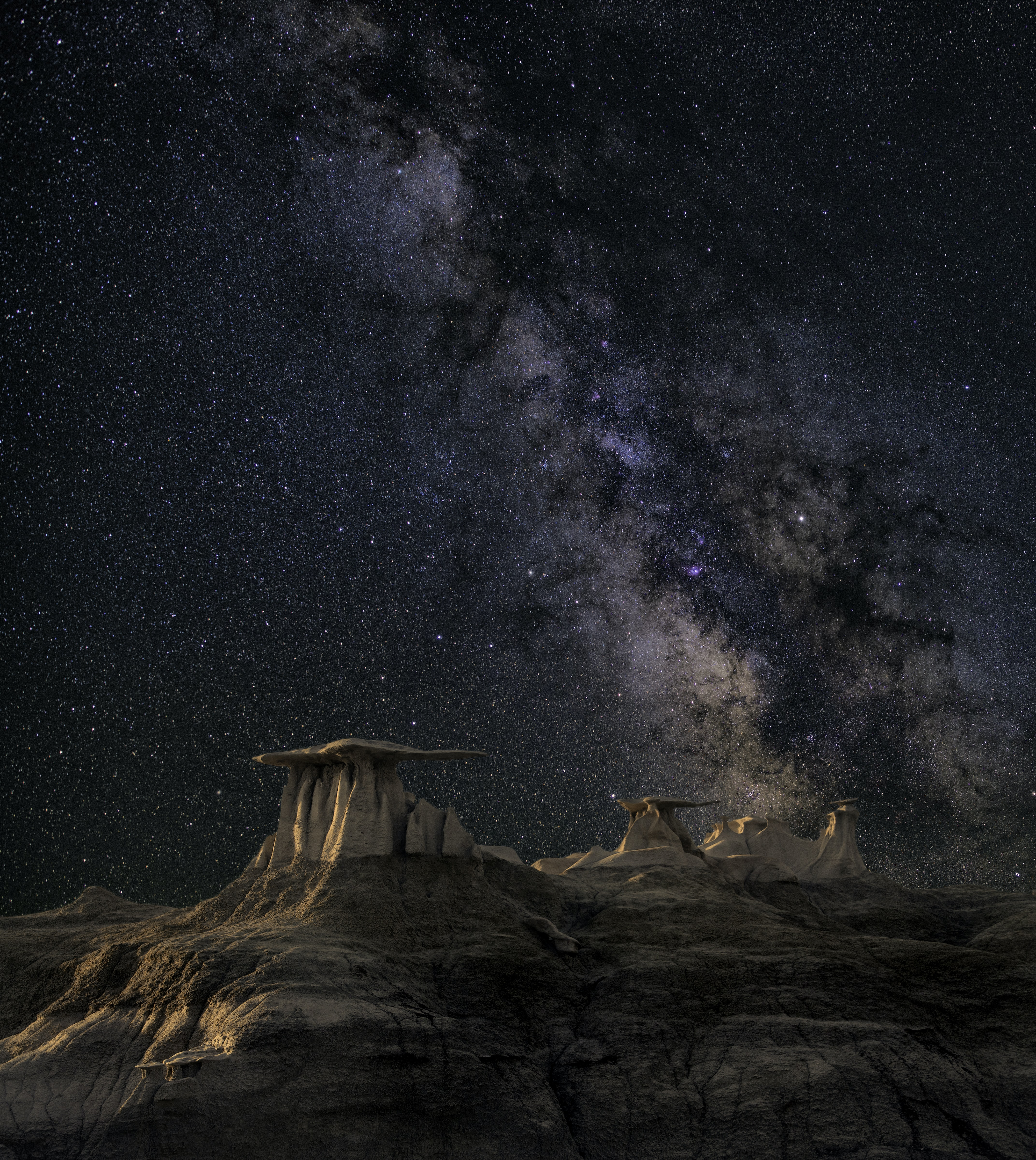 The Milky Way rises above the rock formations against the star-studded night sky.