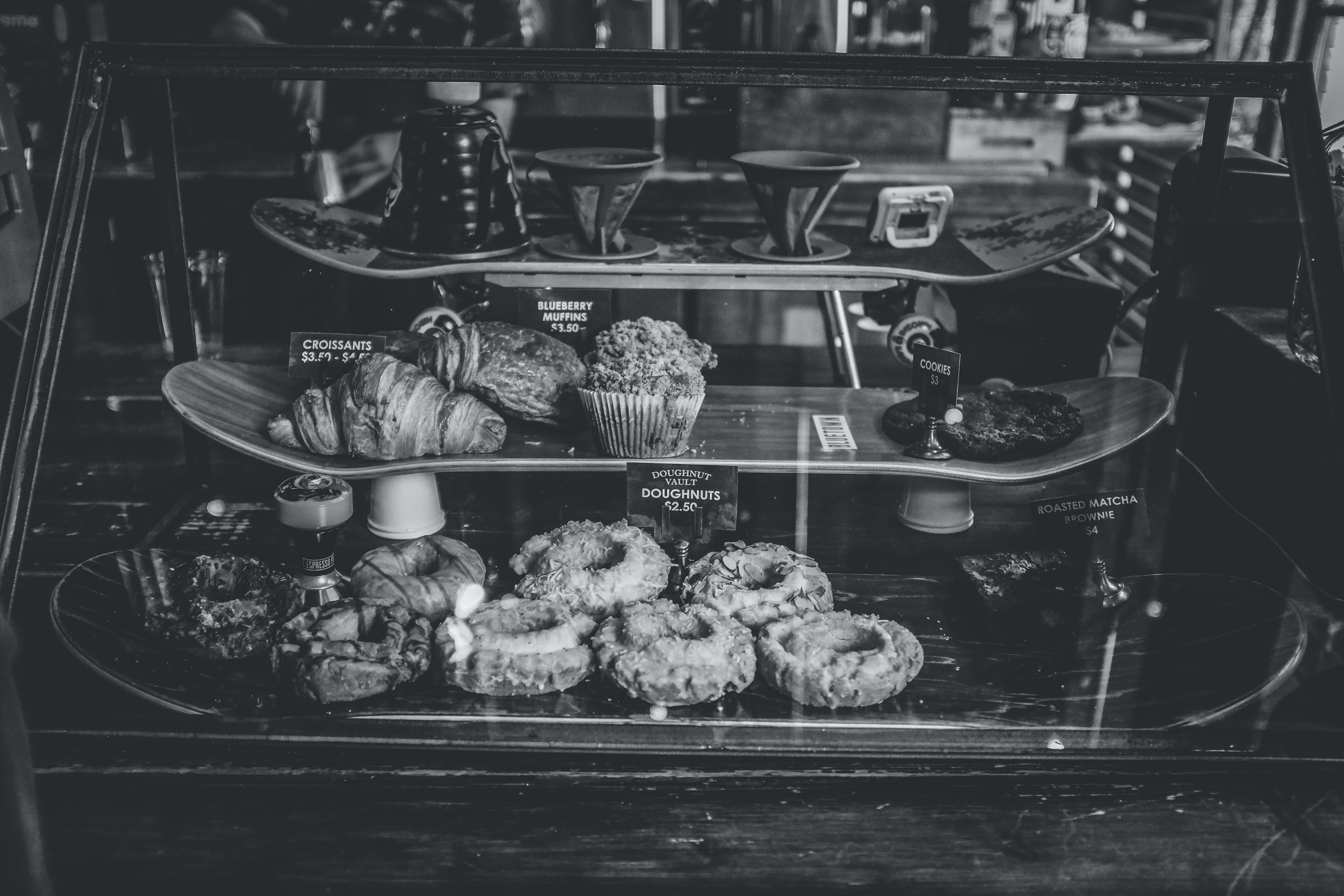 grayscale photo of breads on 3-tier rack