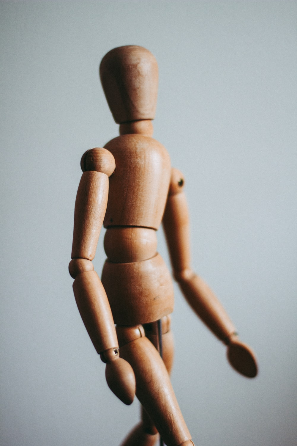 colse-up photo of brown wooden doll
