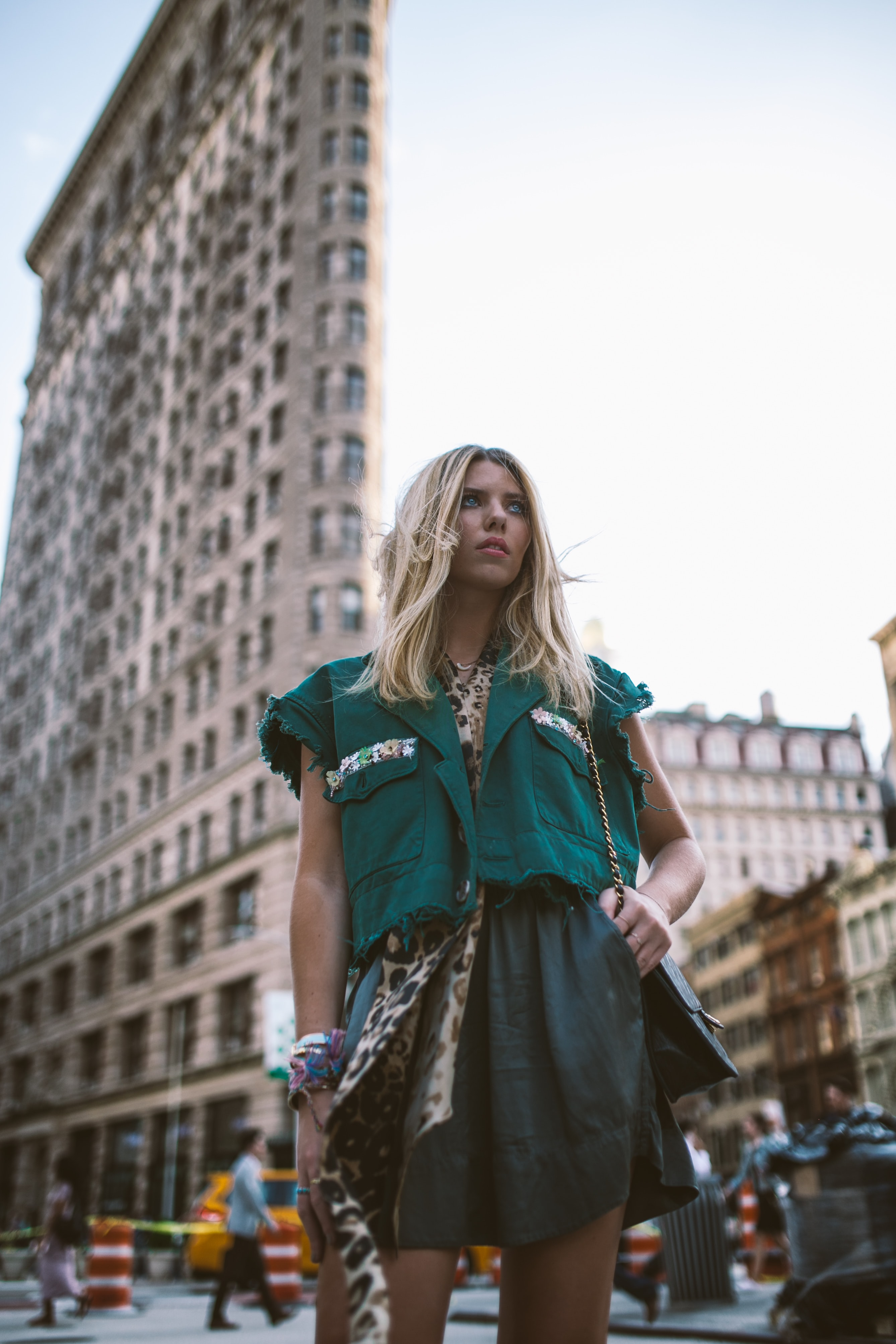 Trendy woman models a blue and green outfit in the city