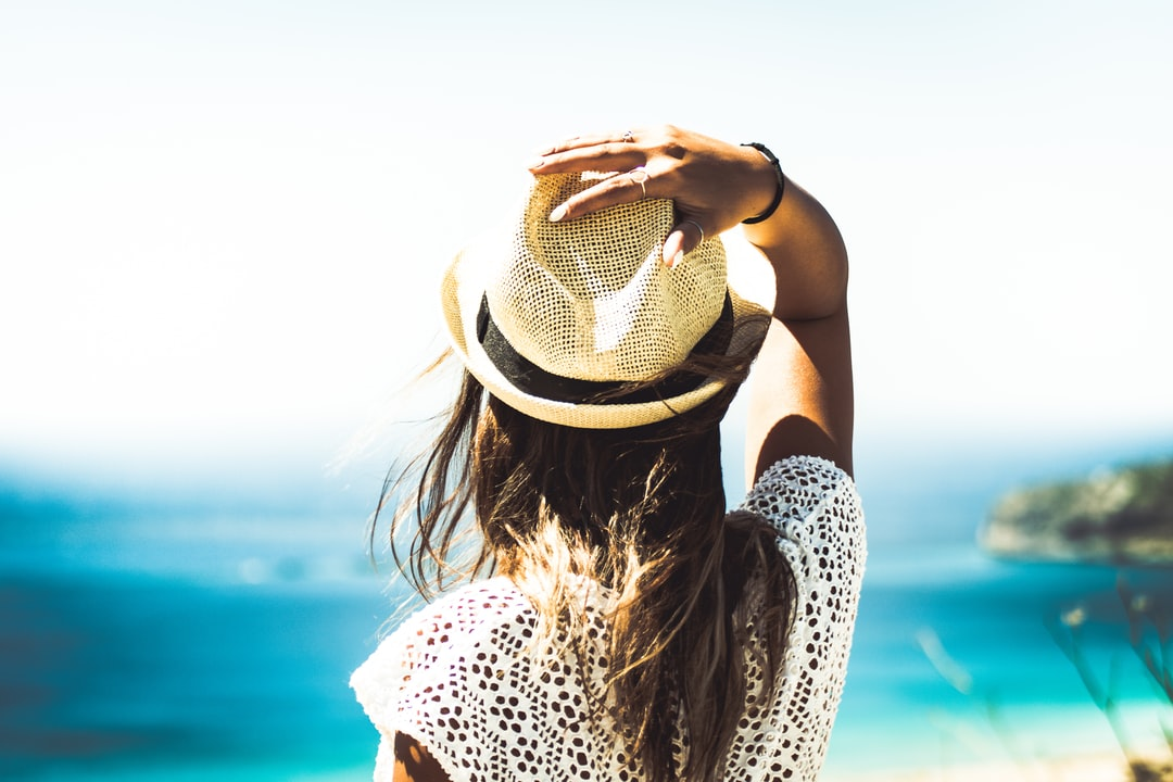 A woman's back as she looks toward the ocean with one hand on her straw hat
