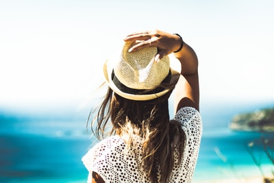woman holding on to her hat summertime zoom background