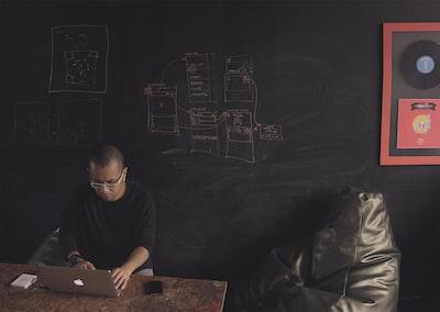 a,man,work,on,a,laptop,at,a,tabl,near,a,chalkboard,wall