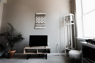 live,room,with,gray,wall,a,tapestri,televis,and,clock,in,corner,near,a,window