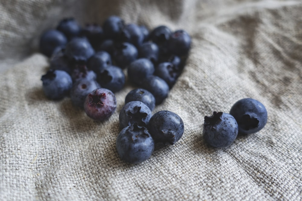 blueberries placed on gray textile