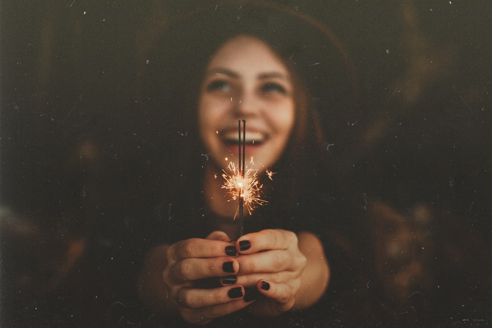 woman holding sparklers while smiling