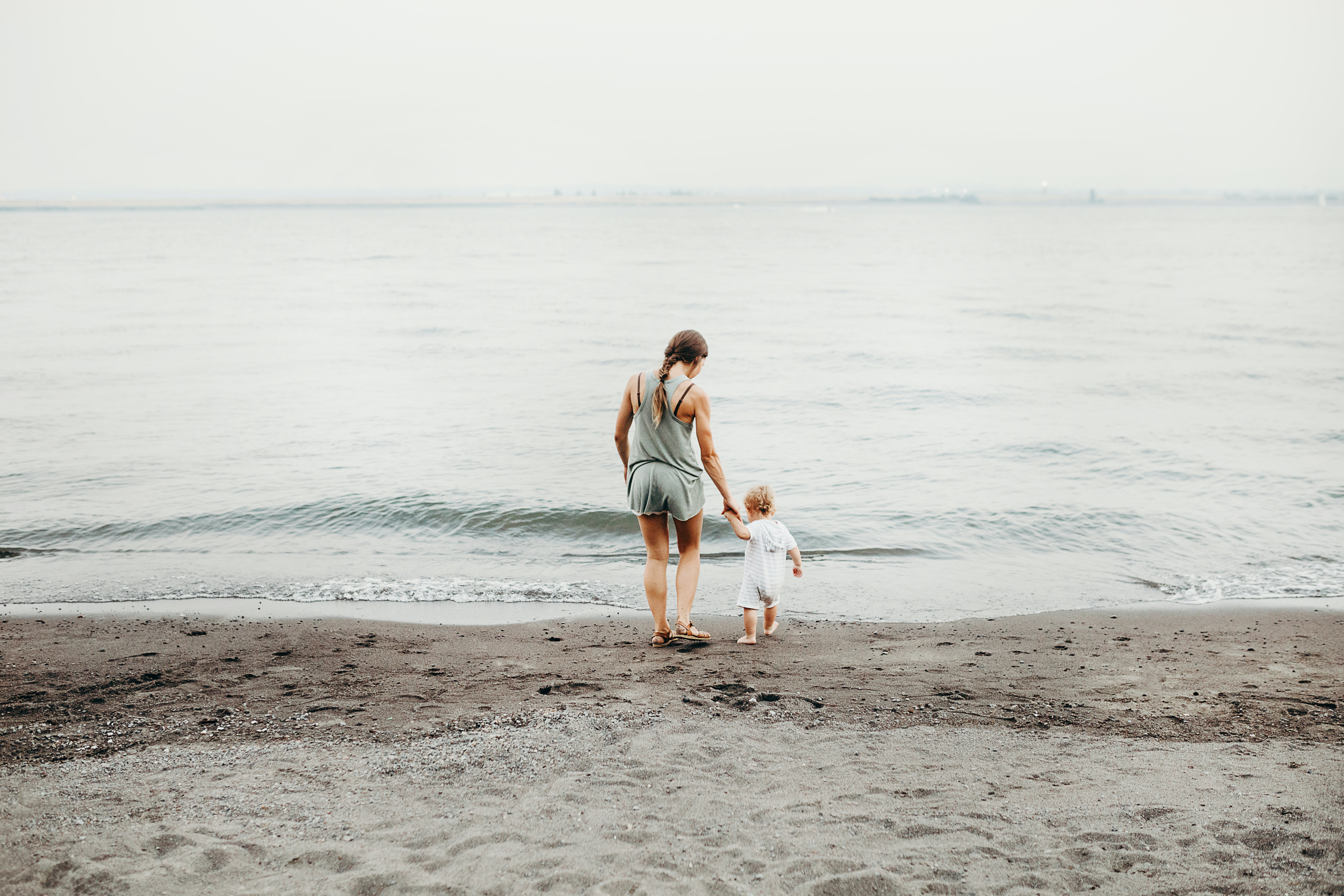 A mother and daughter walking down the beach near the water in Wintler Community Park