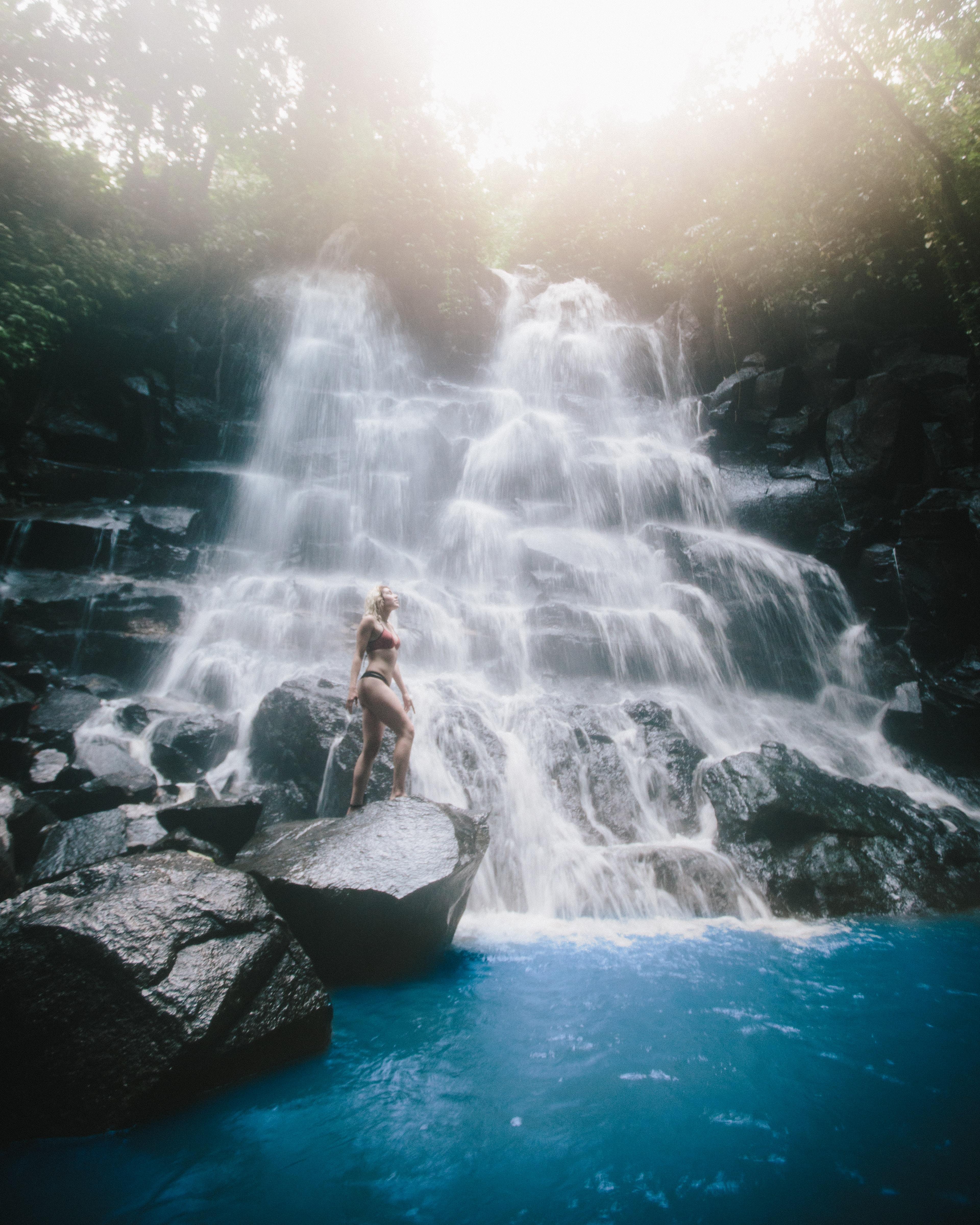A woman in bikini on a wet rock near a waterfall