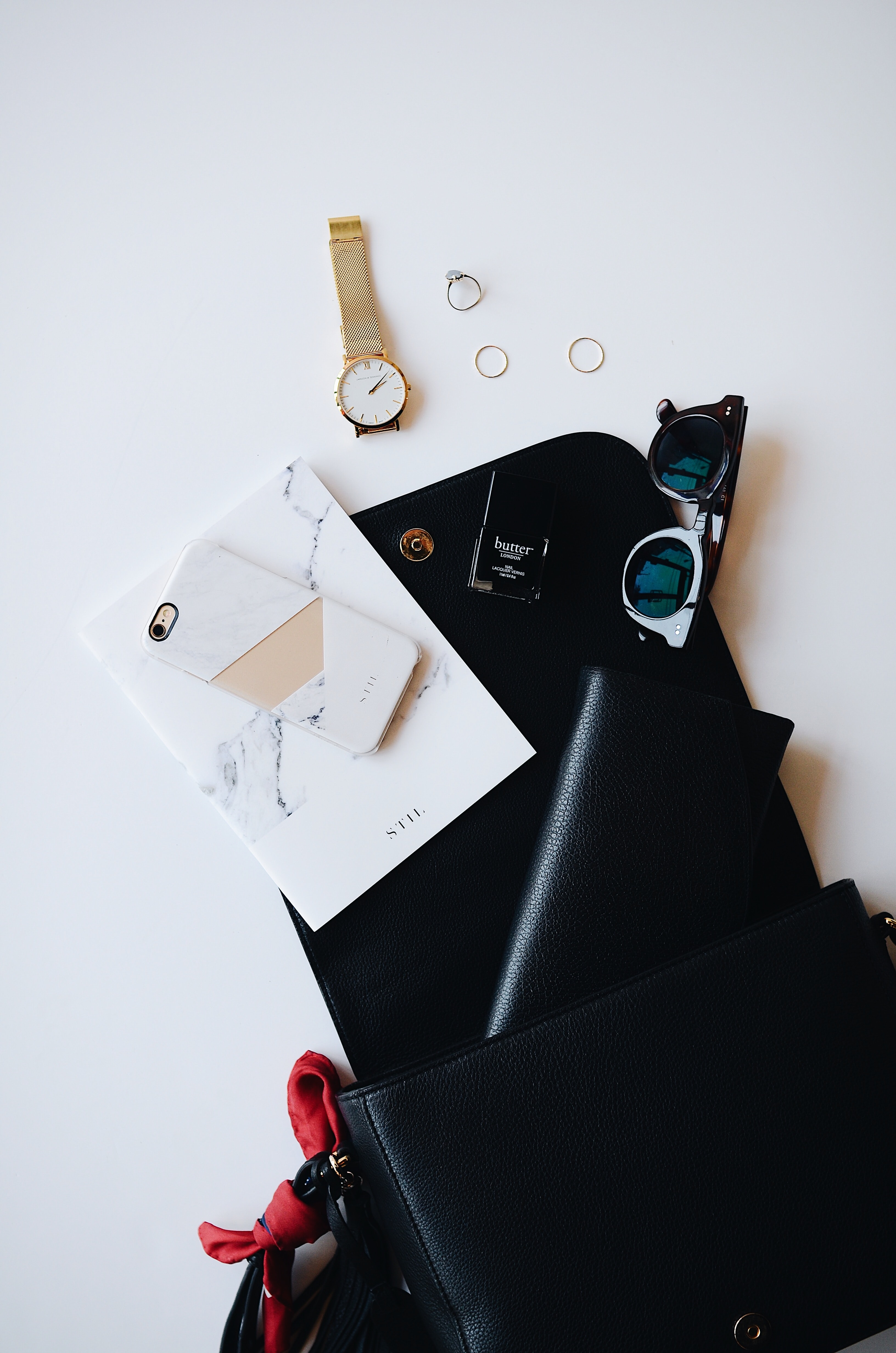 A black clipboard covered with random items, such as a gold watch, white smartphone, leather wallet and pair of glasses.