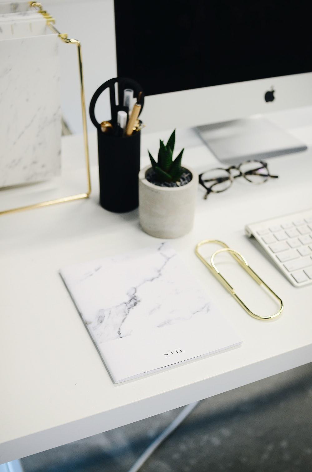 silver iMac and Magic Keyboard on ta ble near white printer paper