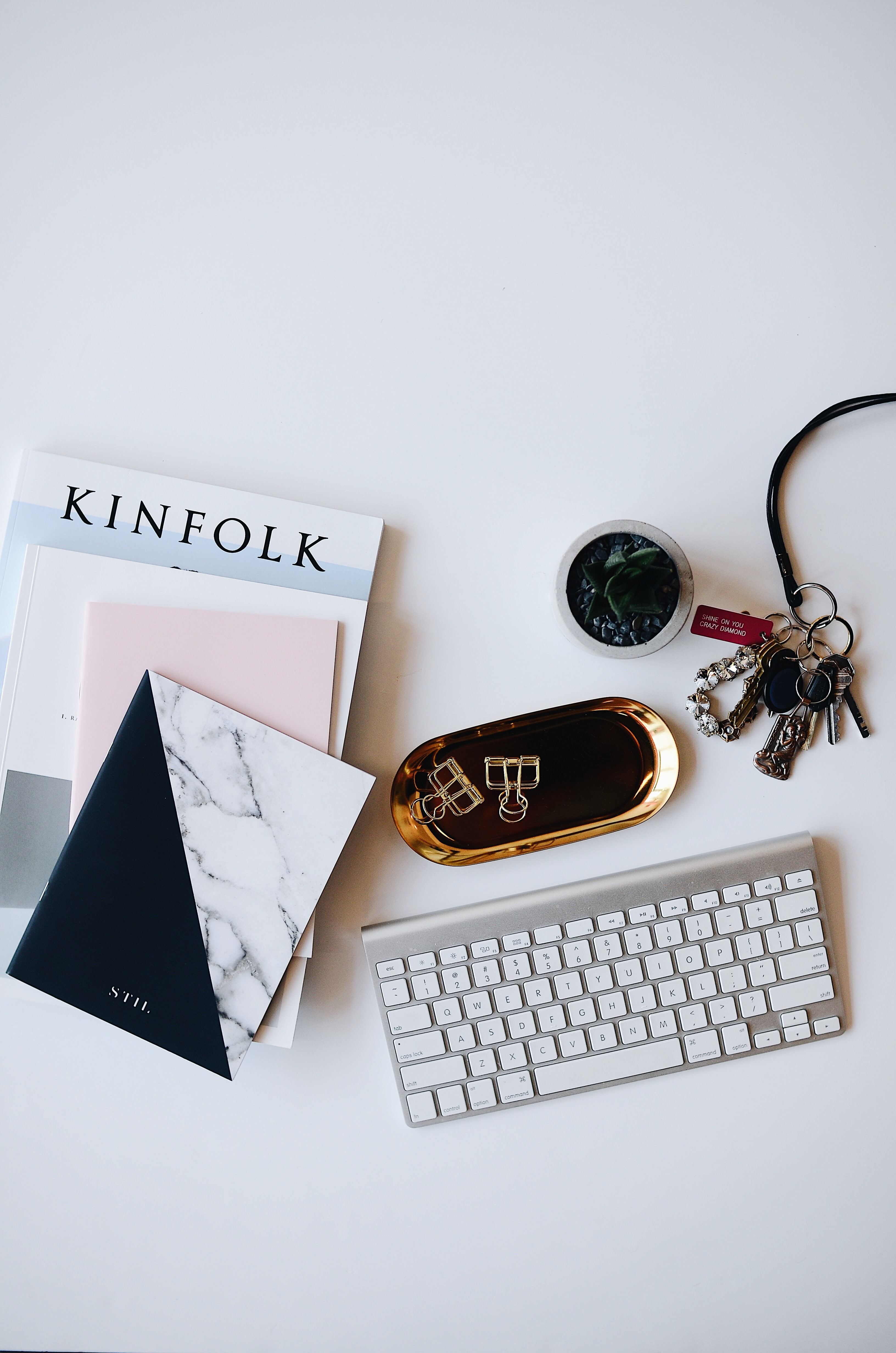 A flatlay image of a keyboard, books and other items.