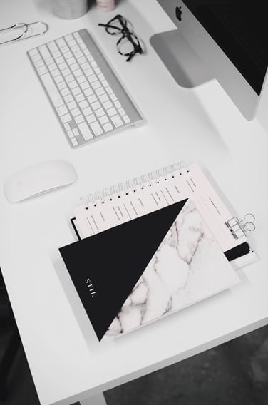 A Spiral Notebook And Book On White Desk With An Imac