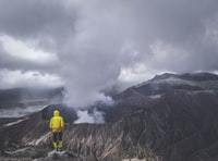 person wearing yellow jacket standing on cliff
