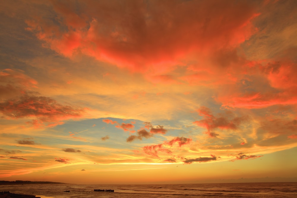 silhouette photo of body of water under orange clouds