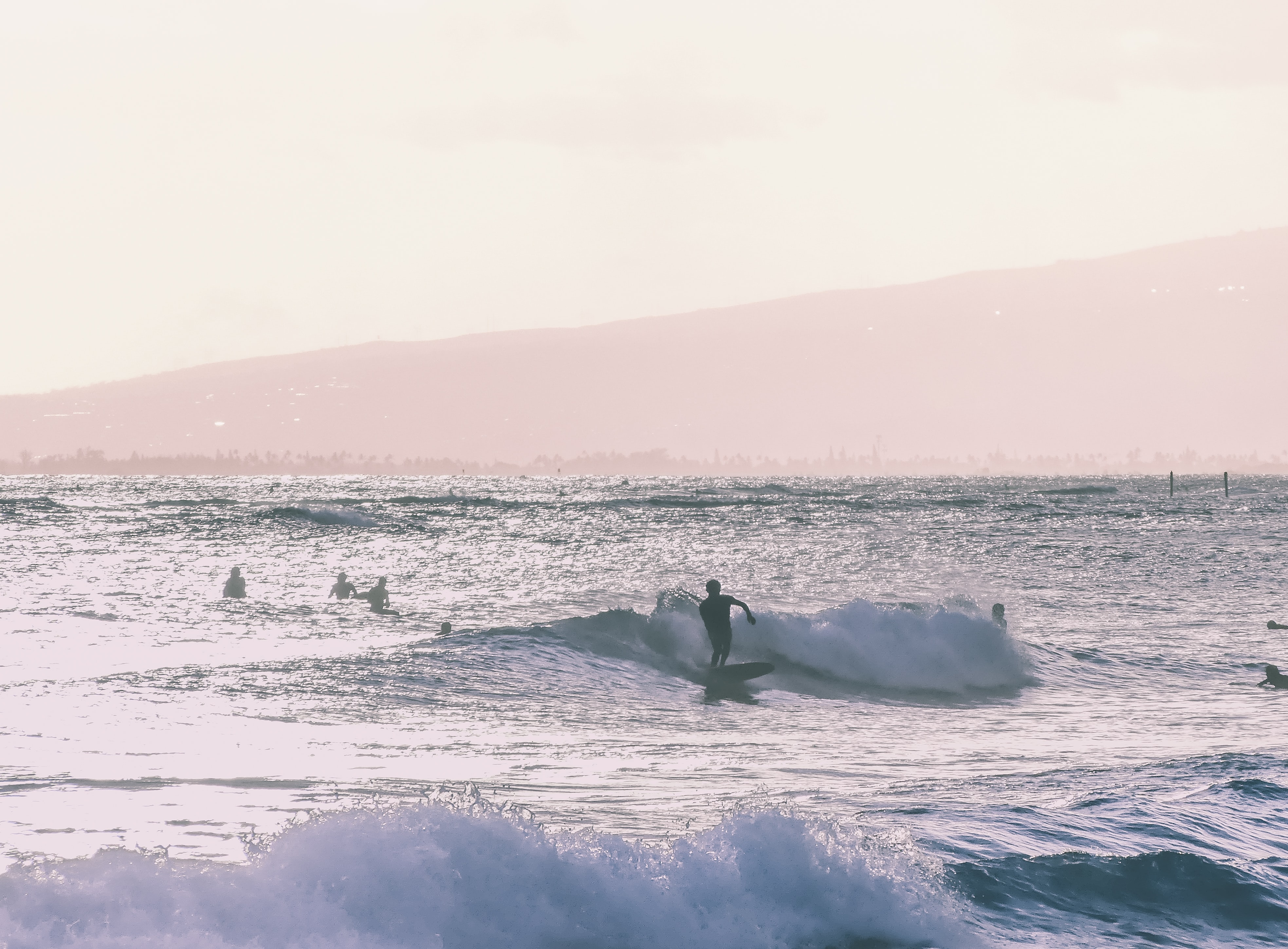 Surfers surfing in the ocean during the day at the Waikīkī Beach