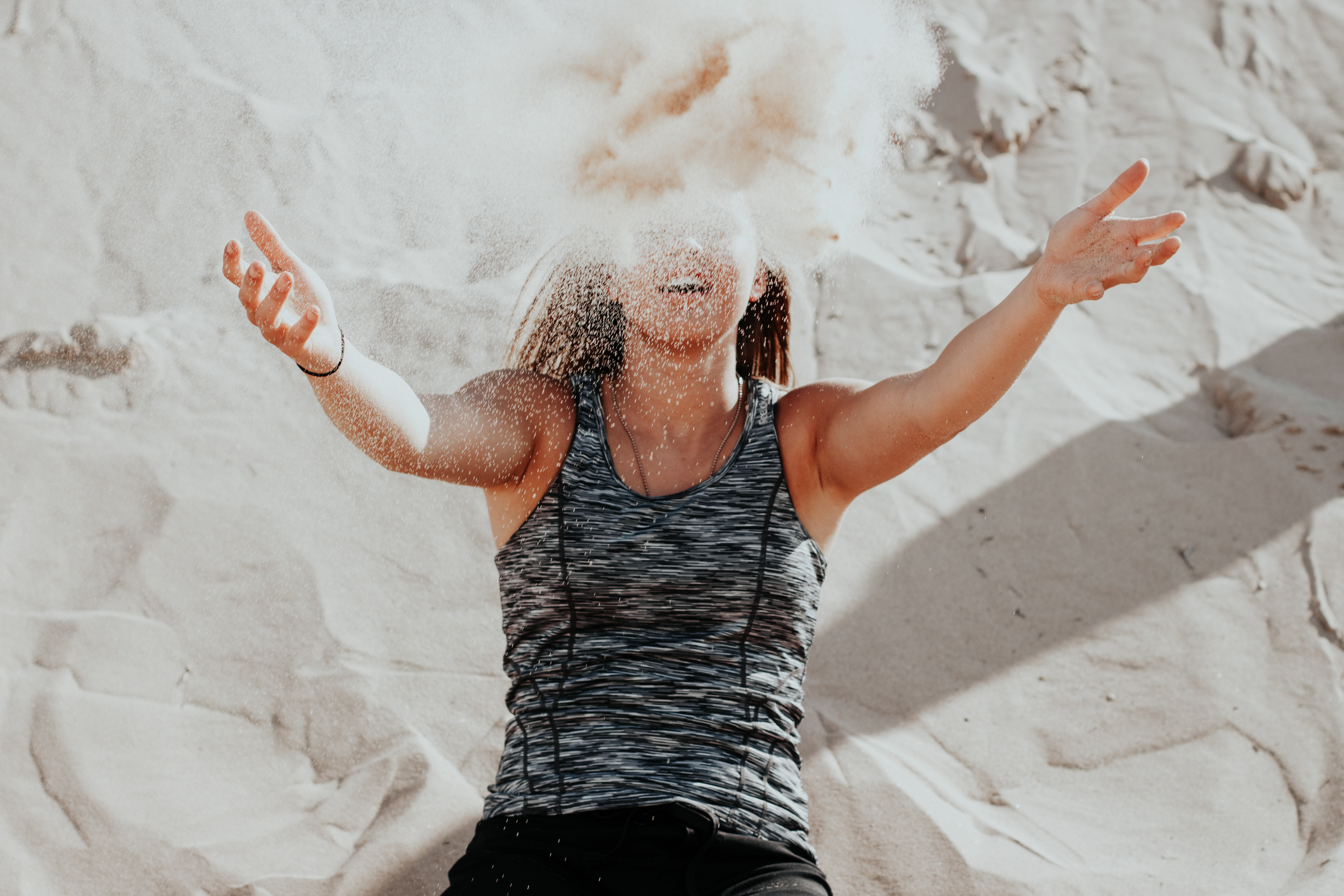 A woman throws sand in front of her face at Sleeping Bear Dunes National Lakeshore