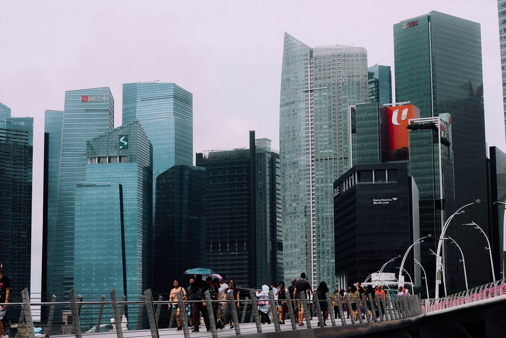 people walking on bridge surrounded with buildings